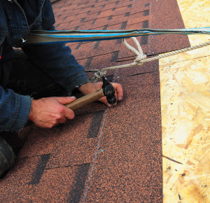 Worker installs bitumen roof shingles - closeup on hands