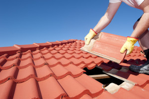 Construction worker tile roofing repair